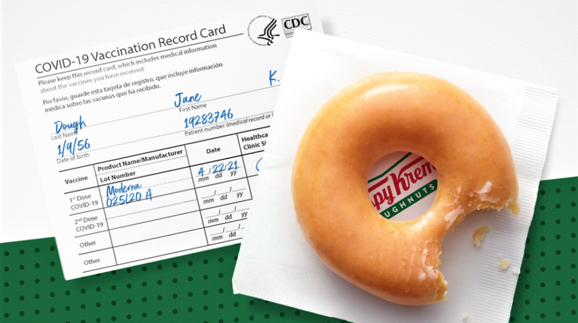 A sample COVID 19 vaccine card alongside a Krispy Kreme glazed doughnut sitting on a napkin; doughnut chain offering free doughnuts to vaccinated individuals