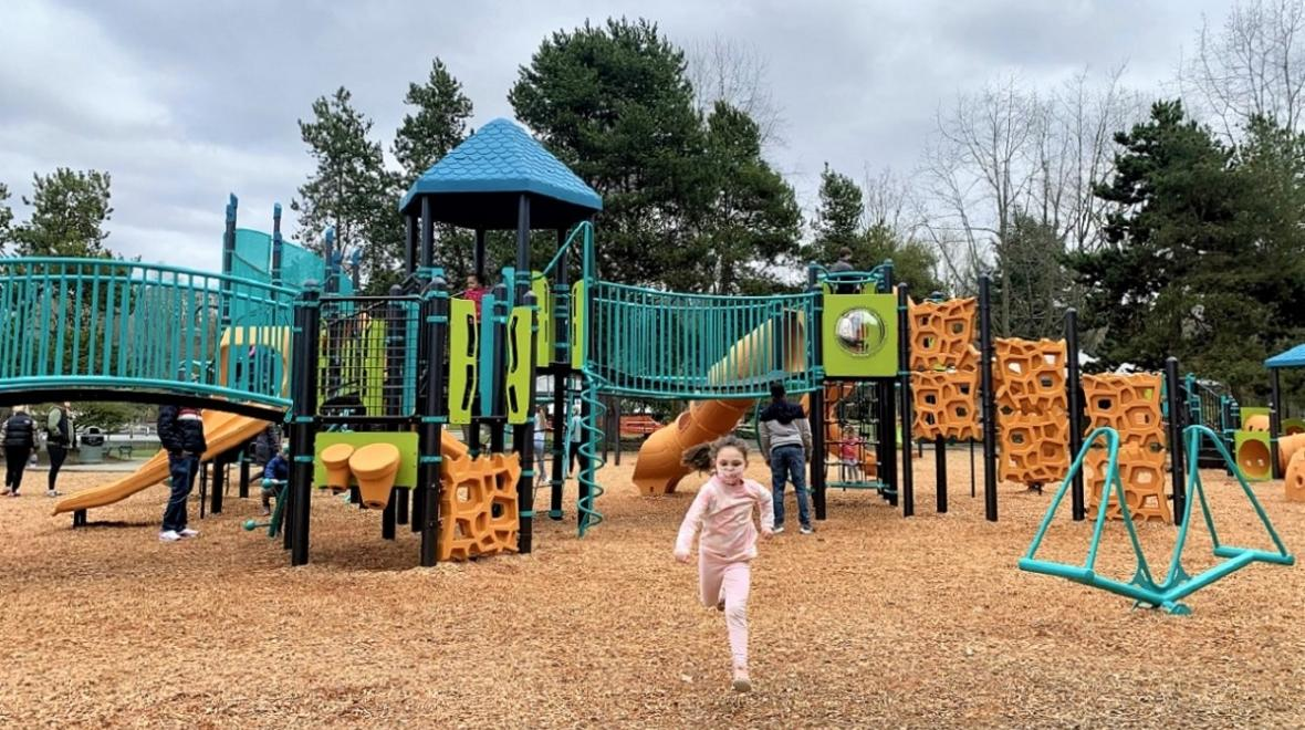 Wide view of new playground at Gene Coulon Memorial Beach Park with girl running in foreground