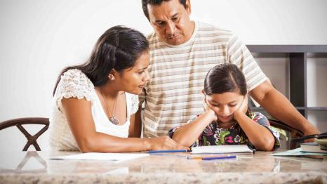 Young girl doing homework with her parents