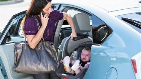 Mom leaving for work and child care with child in infant carseat, bag, phone