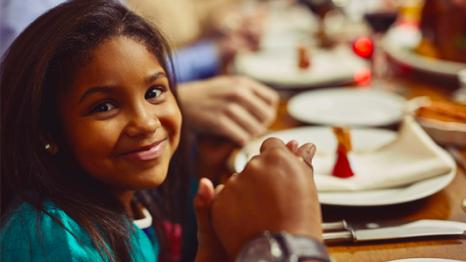 Smiling young girl holding hands at dinner table