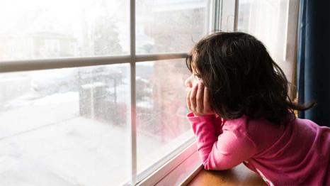 girl looking out the window at snow