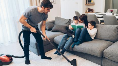 Father vacuums while mother reads a book to their kids