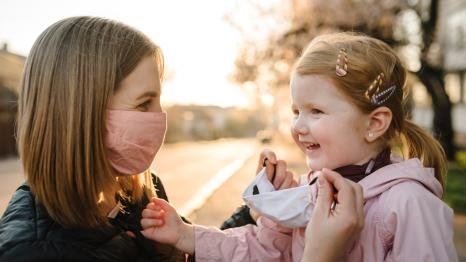 mom putting a mask on her smiling daughter