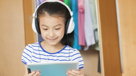 Young girl wearing headphones and viewing content on a tablet computer