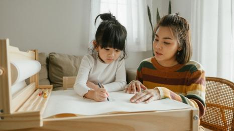 mother and daughter drawing at a child-size table together