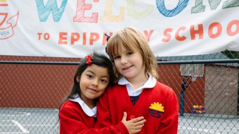 two girls hugging in front of school