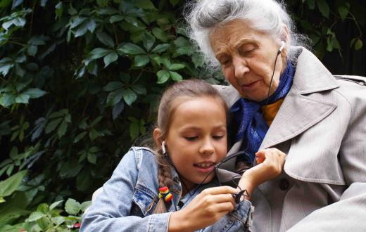 Young girl and grandmother listening to earphones