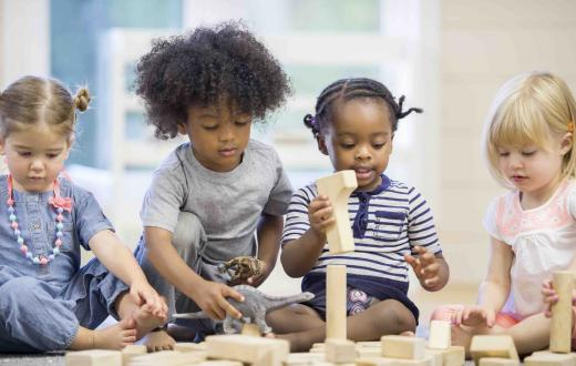 Four preschool kids play with blocks