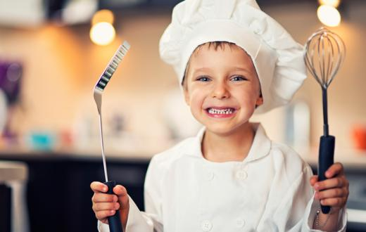 Boy in chef's hat and in kitchen