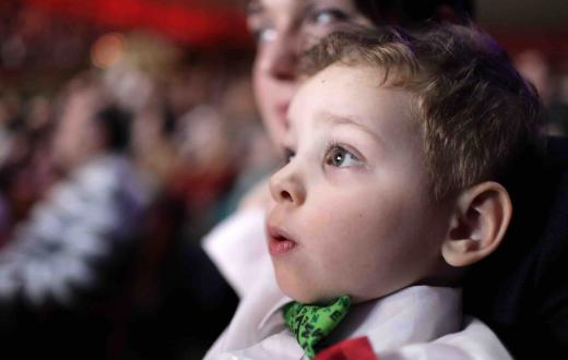 Boy in bow tie watching a show