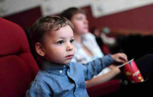 Toddler boy eating popcorn in a movie theater