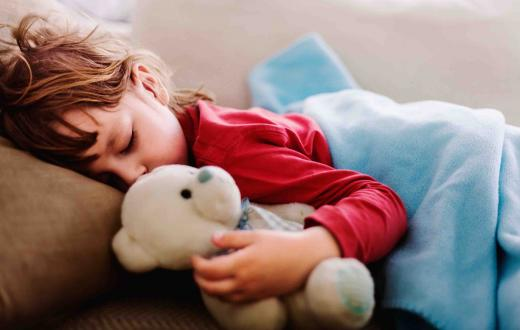 Sleeping child holding teddy bear