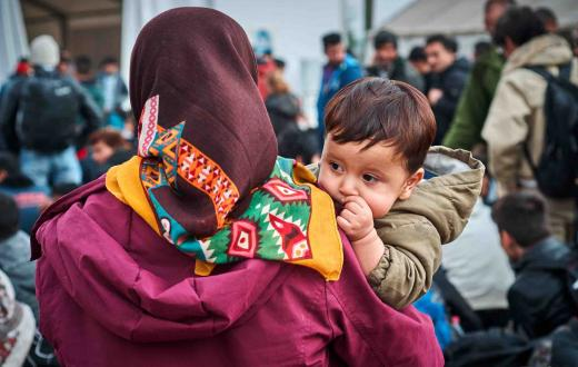 Refugee mother holds son