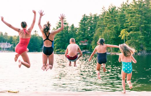 Five kids jumping into a lake