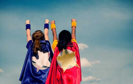 Two girls with superhero capes on