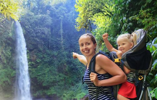 Mother and child hiking by waterfall