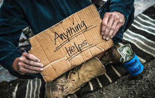Homeless man with cardboard sign