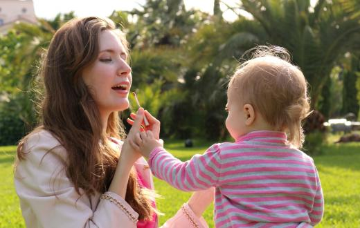 mom-putting-on-makeup-with-baby