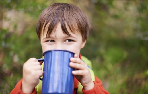 boy drinking from mug while camping