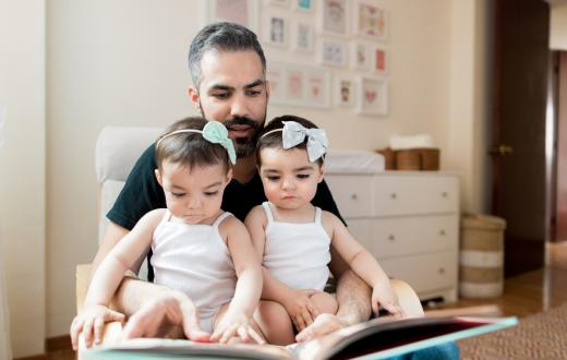 father reading to twin daughters