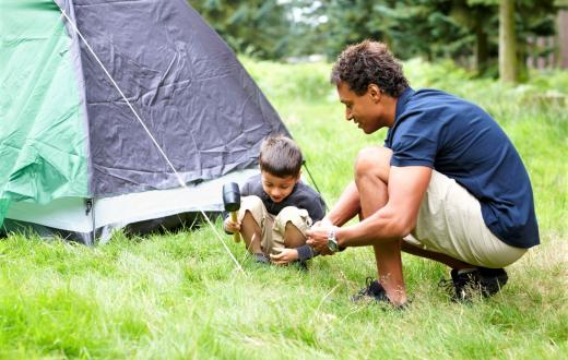 Father and son setting up tent for last-minute camping