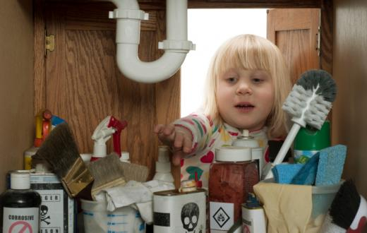 Little girl reaching under the kitchen sink