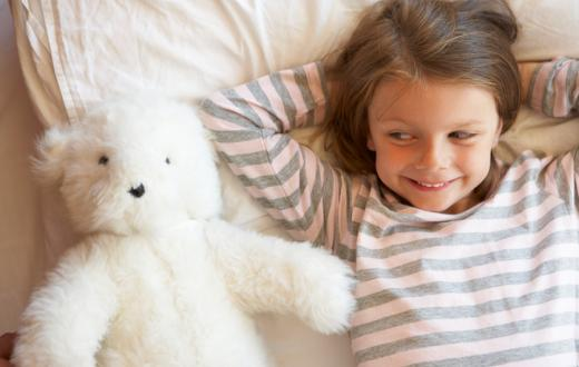 Girl in pajamas with teddy bear