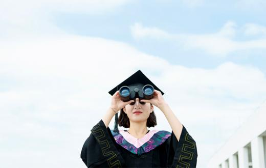 Young woman graduate looking through binoculars