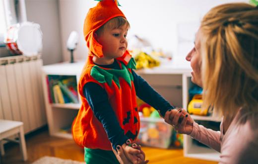 Little boy in Halloween costume with mom