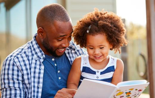 Dad and daughter reading a book