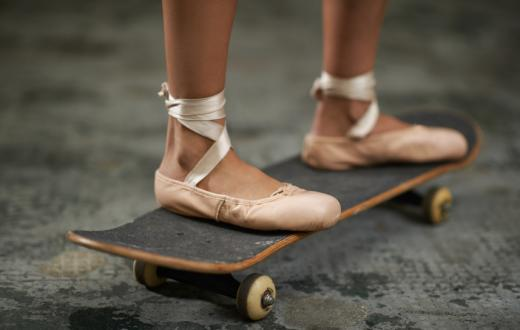 A girl in ballet shoes riding a skateboard