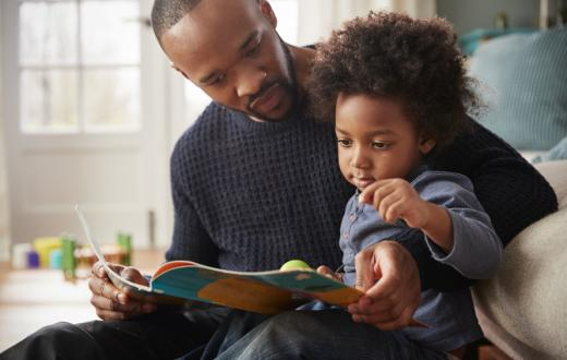 father and kid reading a picture book