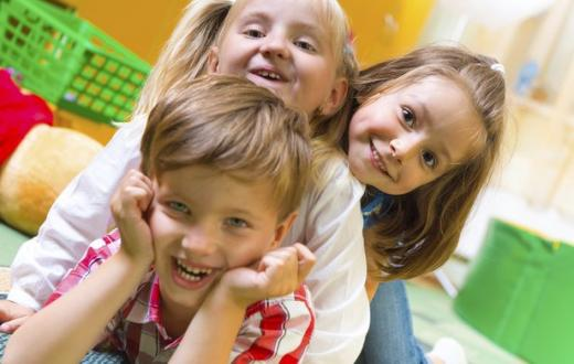 Three children goofing around at preschool