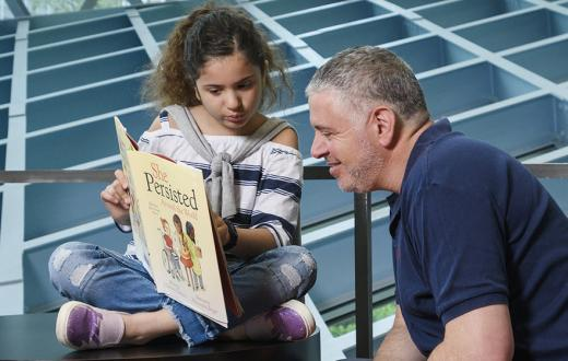 Young girl reads a book to her father at the Seattle Public Library Central Branch