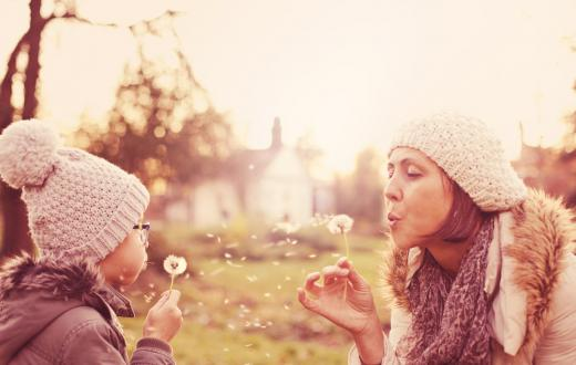 Mom and daughter blowing dandelion seeds