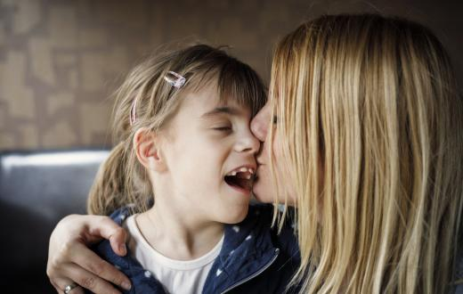 Mom kissing her child with special needs