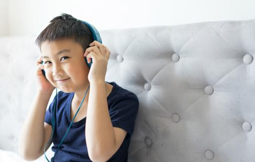 boy listening to a podcast on headphones