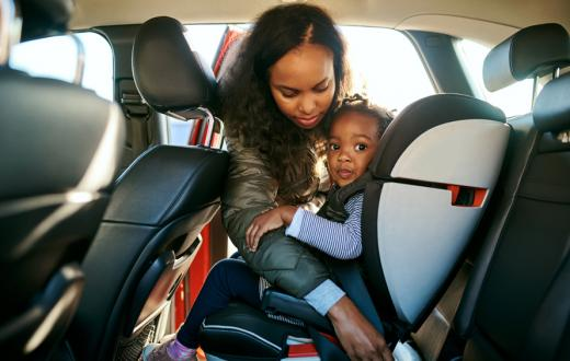mom unbuckling daughters car seat