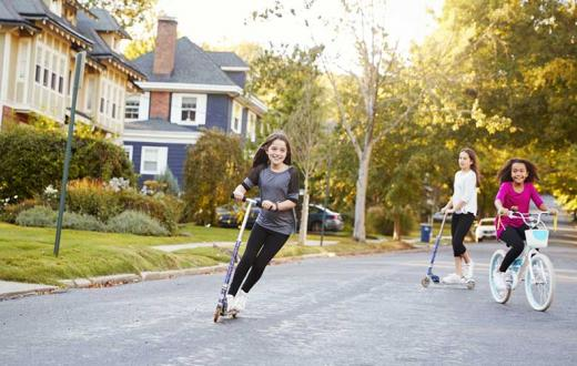 free range girls riding scooters through the neighborhood