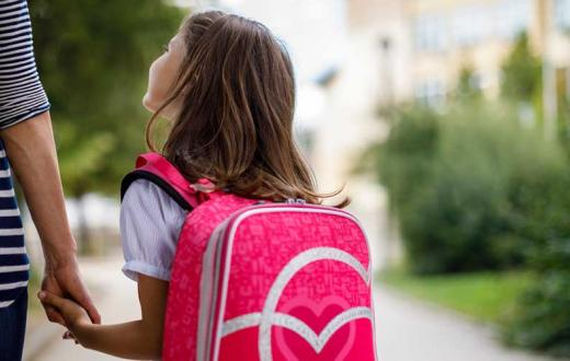 girl with pink back pack holding mom's hand