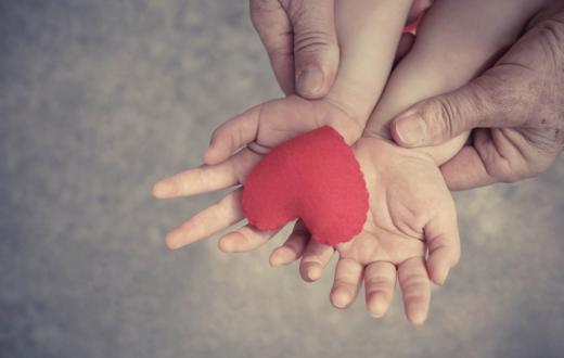 child's hands holding a plush heart