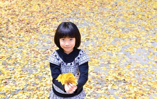 girl holding a bunch of fall leaves