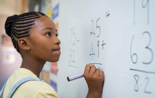 middle school girl doing math on a whiteboard