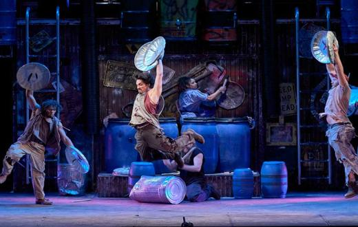 "performer soars through the air in ""STOMP"""
