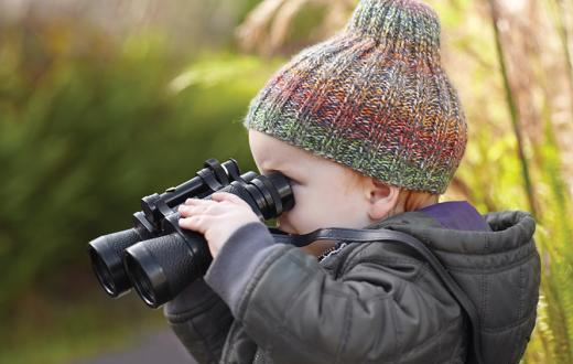 A young boy peers through binoculars
