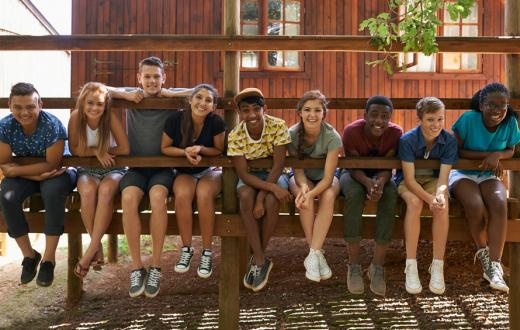 tweens hanging out on cabin doorstep at overnight summer camp
