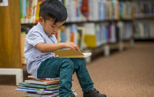 A young boy reads books at a public library