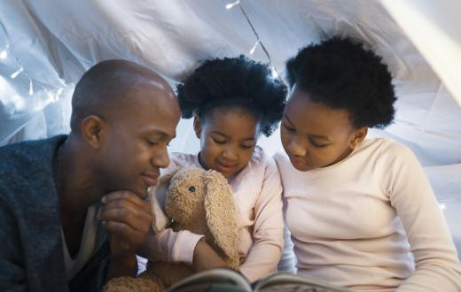 father reading to daughters at bedtime