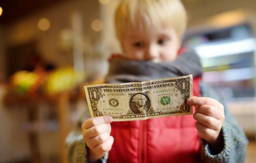 little boy wearing a red jacket holding a dollar bill